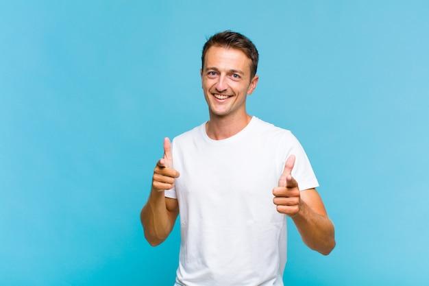 カメラを指して、手で銃のサインを作る前向きな、成功した、幸せな態度で笑って若いハンサムな男