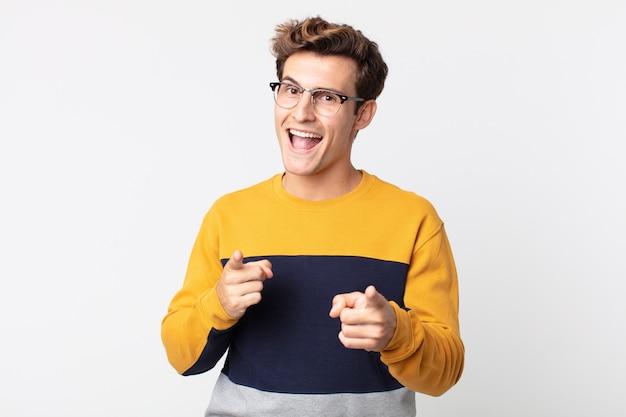 카메라를 가리키는 긍정적이고 성공적이고 행복한 태도로 웃고 있는 젊고 잘생긴 남자, 손으로 총기 표지 만들기