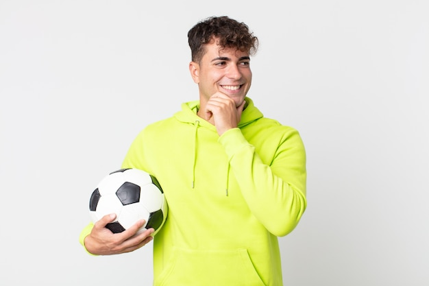 Young handsome man smiling with a happy, confident expression with hand on chin and holding a soccer ball