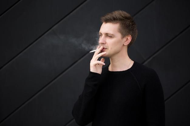 Молодой красавец курит сигарету