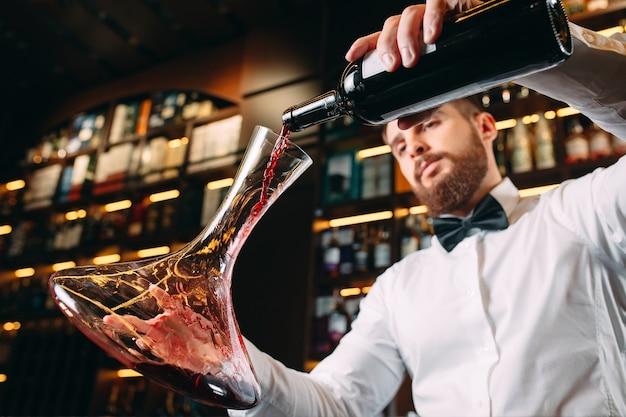セラーで赤ワインを味わう若いハンサムな男のソムリエ