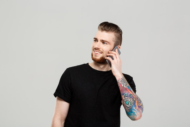 Young handsome man speaking on phone over grey wall.
