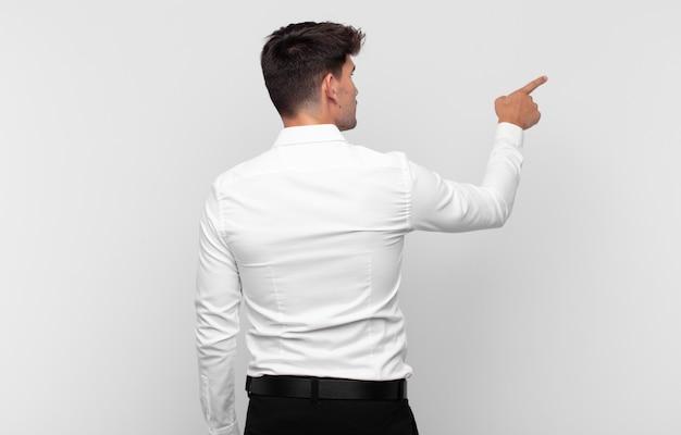 立ってコピースペース、背面図上のオブジェクトを指している若いハンサムな男