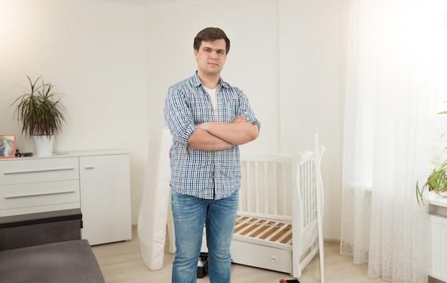 분해된 아기 침대에 서 있는 젊은 잘생긴 남자