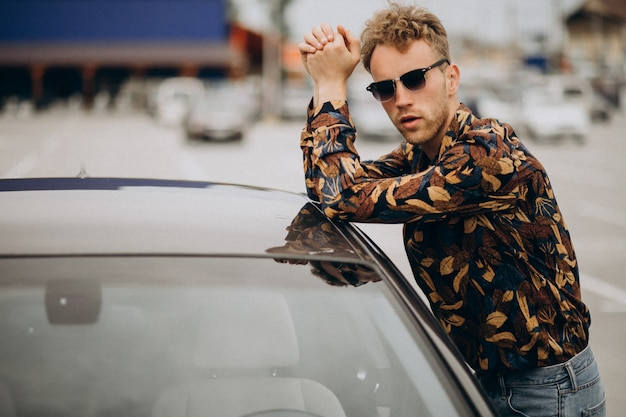 Young handsome man standing by car