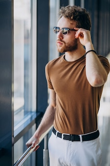 空港の窓のそばに立っている若いハンサムな男