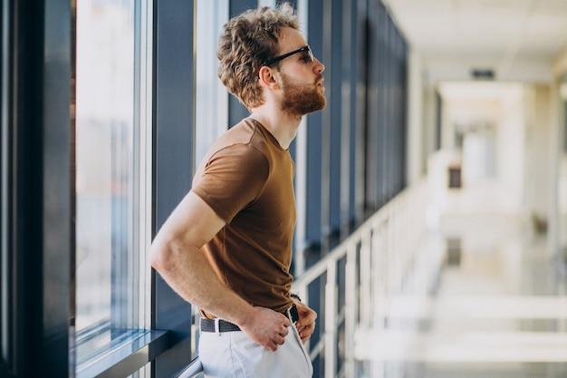 Молодой красавец, стоя у окна в аэропорту