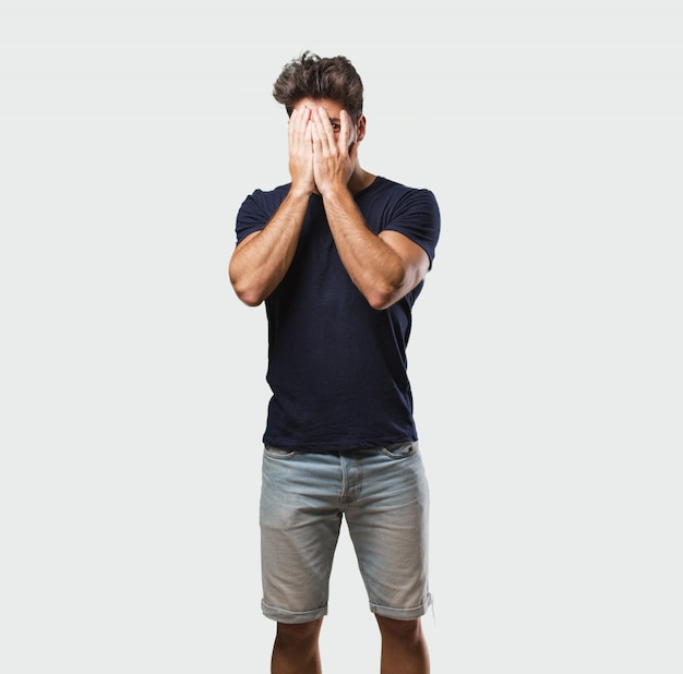 Young handsome man standing feels worried and scared, looking and covering face, concept of fear and anxiety