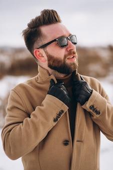 Молодой красивый мужчина стоял в зимнем парке, портрет