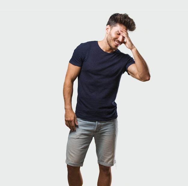 Young handsome man standing laughing and having fun, being relaxed and cheerful