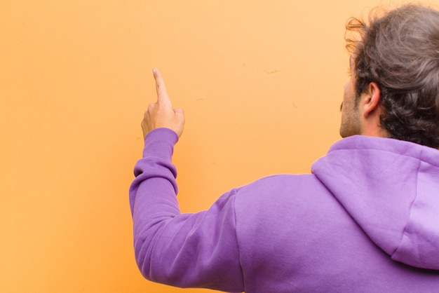 Young handsome man standing and pointing to object on copy space, rear view against orange wall