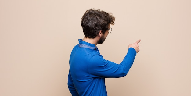 Young handsome man standing and pointing to object on copy space, rear view on flat wall