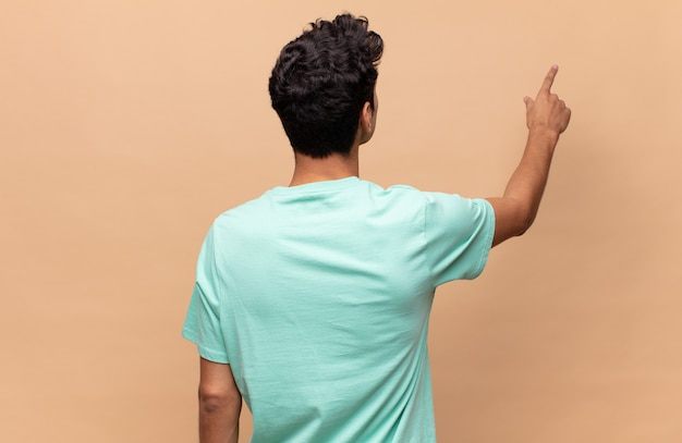 Young handsome man standing and pointing to object on copy space, rear view