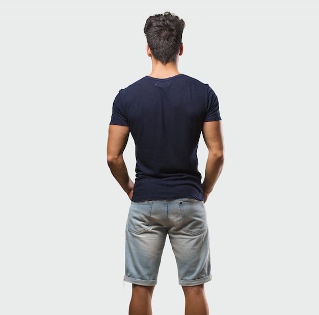 Young handsome man standing showing back, posing and waiting, looking back