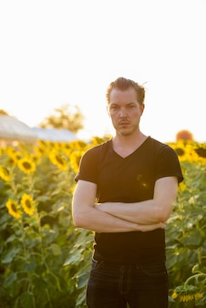 Молодой красавец, стоящий со скрещенными руками в поле