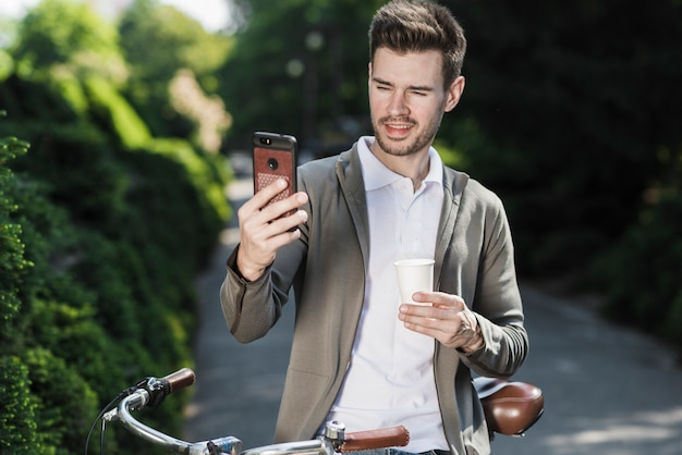 Young handsome man standing with bicycle taking selfie on mobile phone