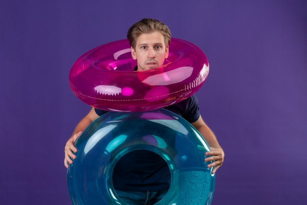 Young handsome man standing with inflatable rings looking at camera surprised scared over purple background