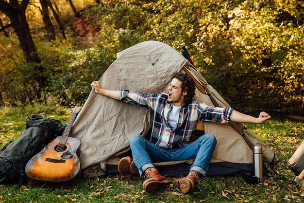 Young handsome man stretches in the morning near the tent in the camping in nature
