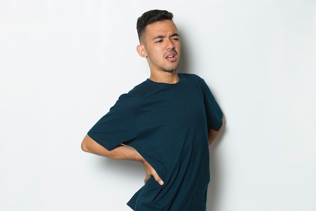 Young handsome man suffering low back pain and waist lumbar pain on white background