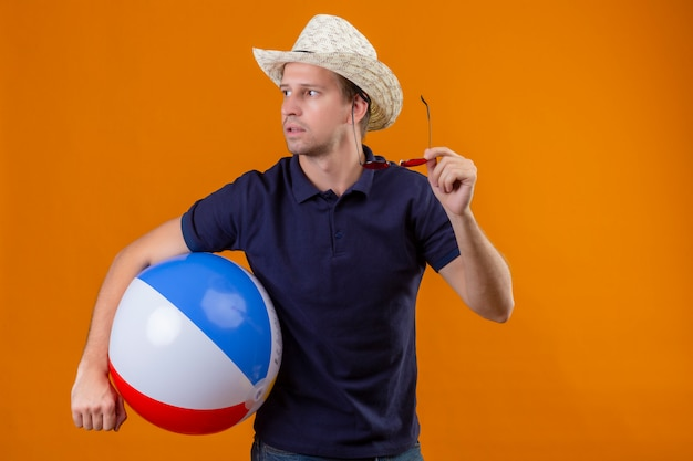 Young handsome man in summer hat holding inflatable ball and sunglasses looking aside with serious face uncertain look standing over orange background