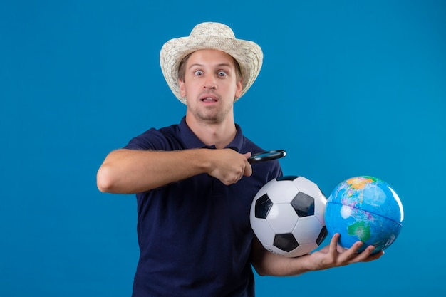 Giovane uomo bello in cappello estivo tenendo palla da calcio e globo andando a guardare il globo attraverso la lente di ingrandimento guardando sorpreso e stupito in piedi su sfondo blu
