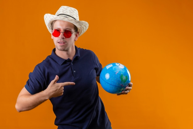 Young handsome man in summer hat wearing red sunglasses holding globe pointing finger to it with confident expression on face standing over orange background