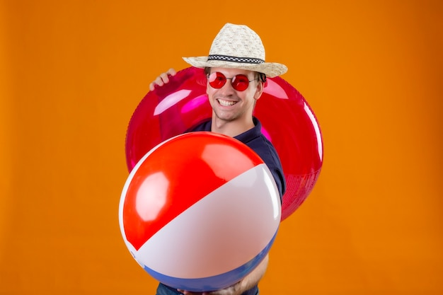 Young handsome man in summer hat wearing red sunglasses holding inflatable ball and ring looking at camera with confident smile self-satisfied standing over orange background