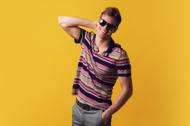 Young handsome man in sunglasses wearing casual t-shirt standing over yellow wall looking with smile on face, natural expression. laughing confident.