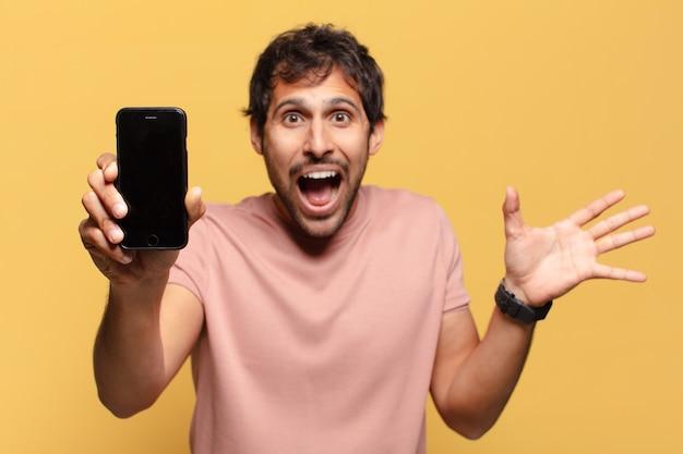 若いハンサムな男は表情スマートフォンのコンセプトを驚かせた