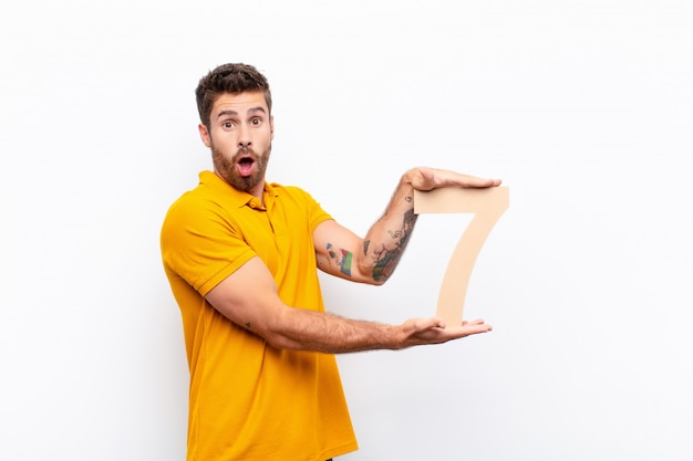 Young handsome man surprised, shocked, amazed, holding a number 7.