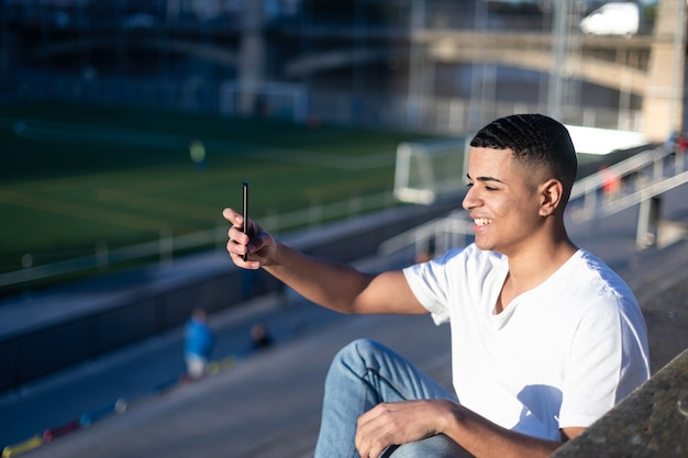 A young handsome man in t-shirt and jeans sits on a stadium bleachers and takes a picture