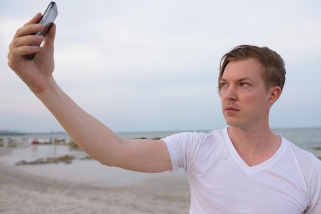 Молодой красавец, делающий селфи с мобильным телефоном