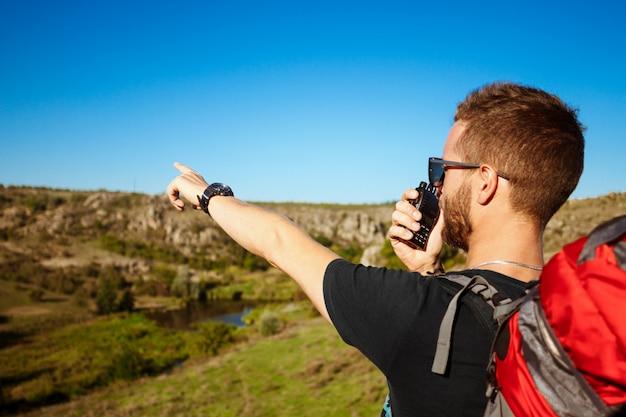 Молодой красивый мужчина разговаривает по рации, наслаждаясь видом на каньон