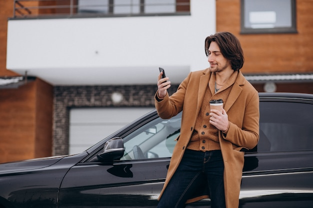 Young handsome man talking on the phone by his car