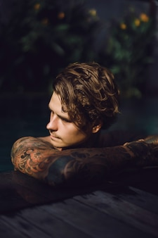 Young handsome man in tattoos resting in the outdoor pool.