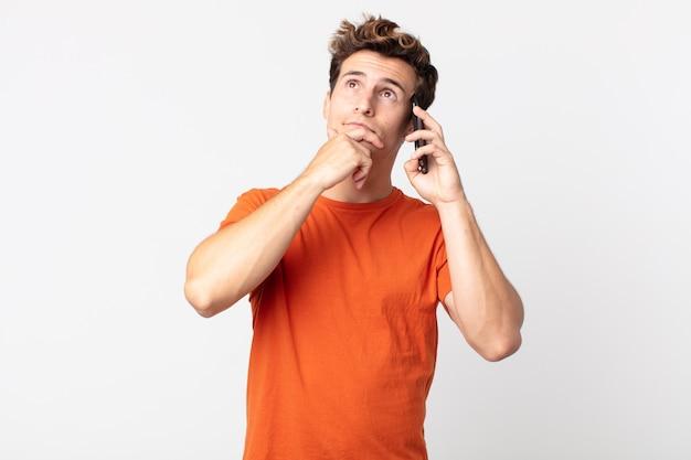 젊고 잘생긴 남자는 생각하고 의심스럽고 혼란스러워하며 스마트 폰으로 이야기합니다.