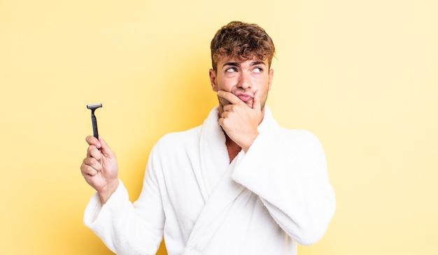 Молодой красавец думает, сомневается и смущается. концепция бритья
