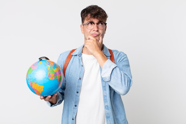 考えて、疑わしくて混乱している若いハンサムな男。世界の地球地図を持っている学生