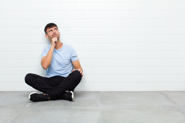 Young handsome man thinking, feeling doubtful and confused, with different options, wondering which decision to make sitting on cement floor
