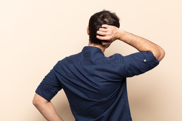 생각하거나 의심하는 젊은 잘 생긴 남자, 머리를 긁적, 의아해하고 혼란스러워하는 느낌, 뒤로 또는 후면보기