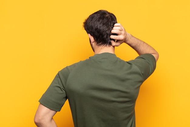 考えたり疑ったり、頭を掻いたり、困惑したり混乱したり、背面図または背面図の若いハンサムな男