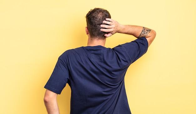 Молодой красивый мужчина думает или сомневается, почесывает голову, чувствует недоумение и замешательство, вид сзади или сзади
