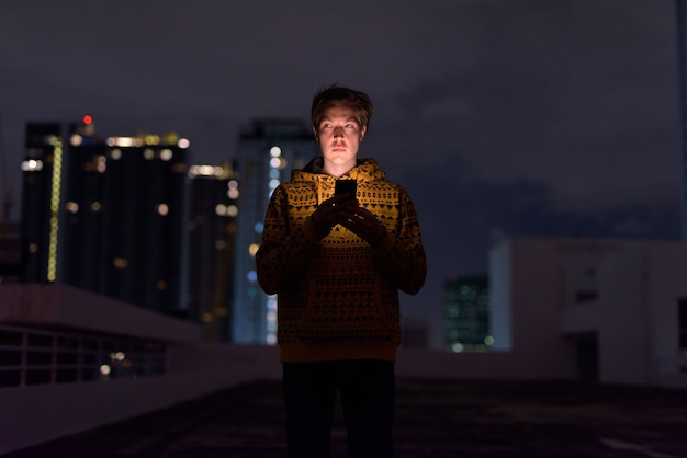 夜の荒天時に街の景色に対して電話を使用しながら考えて若いハンサムな男