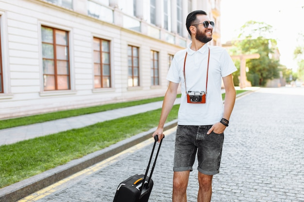 Young and handsome man tourist with a beard, walking around the city with a suitcase and a camera on his neck
