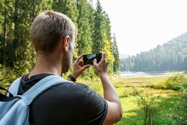Young handsome man traveling, taking photo of beautiful mountains view