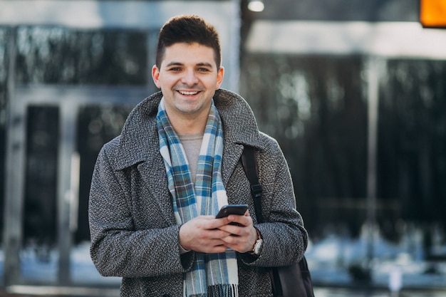 Young handsome man traveller using phone outside