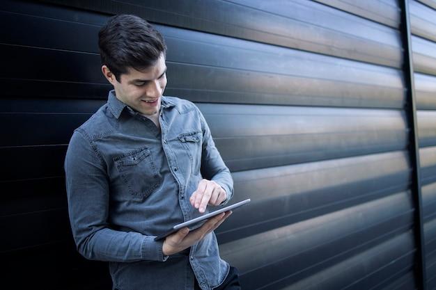 彼のタブレットコンピューターで入力する若いハンサムな男