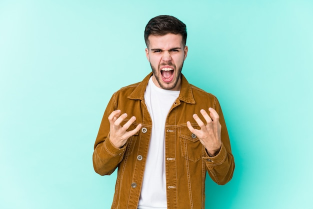 Young handsome man upset screaming with tense hands.