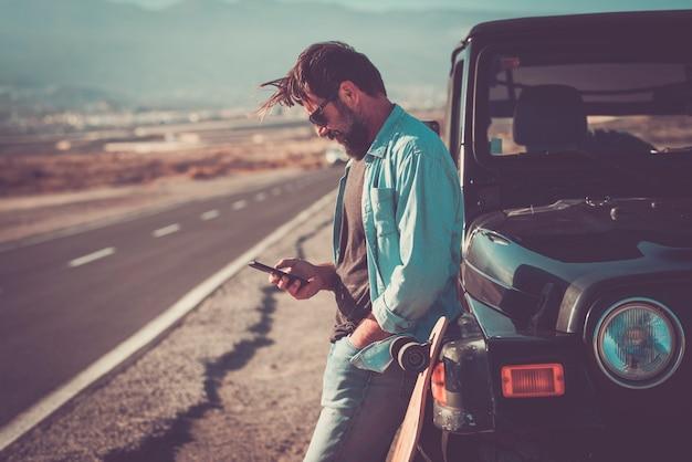 若いハンサムな男は、バックグラウンドで長い道のりで黒い車の車の外で携帯電話を使用します-ローミングインターネットワイヤレス接続技術で旅行者の冒険の概念