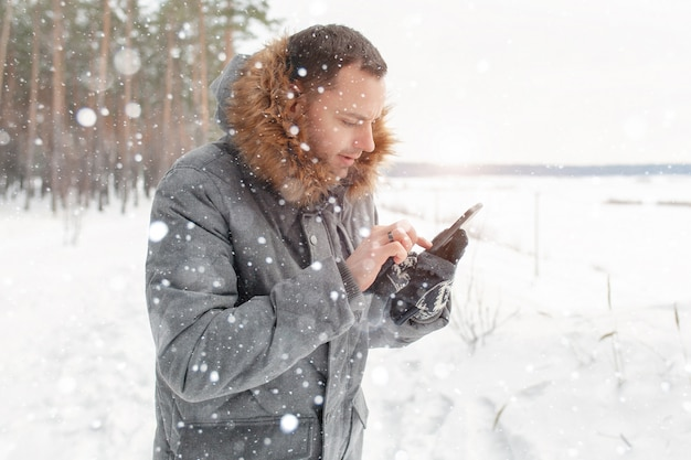 A young handsome man uses a mobile phone in a snowy forest.